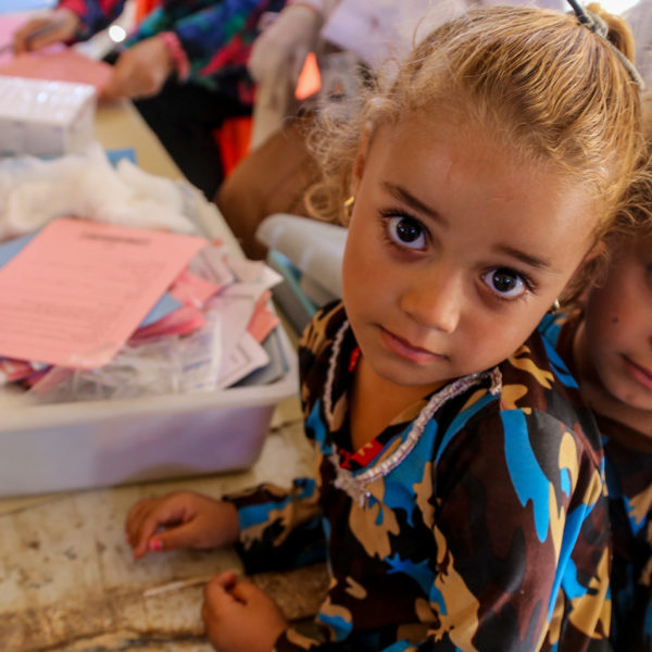 Two girls wait in line at a temporary medical centre in Iraq. Unicef/2016/Kuzaie