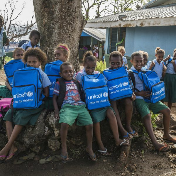 Children proudly hold their new school bags. After a disturbing event like Cyclone Pam it's important to get children back to learning and playing as soon as possible.