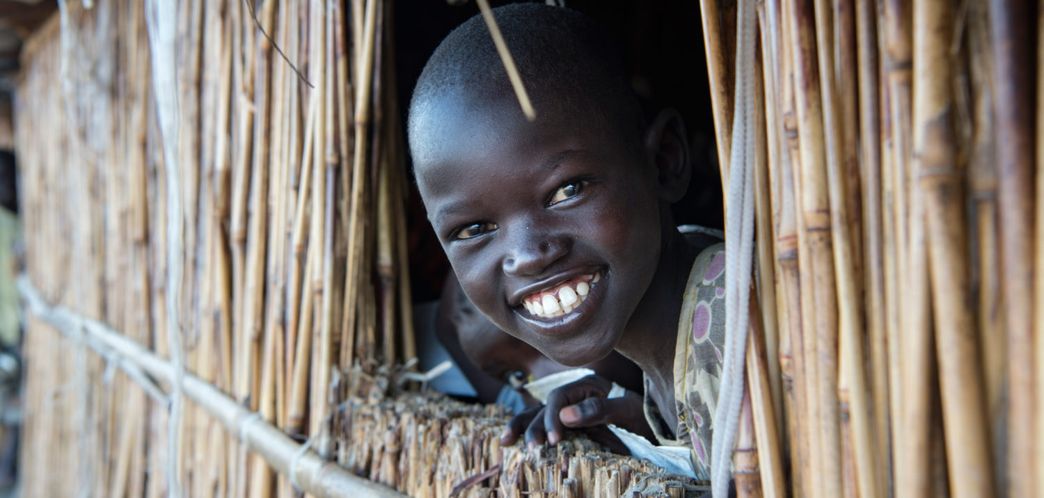 A young girl smiles as she looks out a classroom window at Lich Primary School, located at the Bentiu Protection of Civilians (POC) site, at the UNMISS (United Nations Mission in South Sudan) base near the city of Bentiu, capital of Unity State. Photo: Unicef/2016/Everett