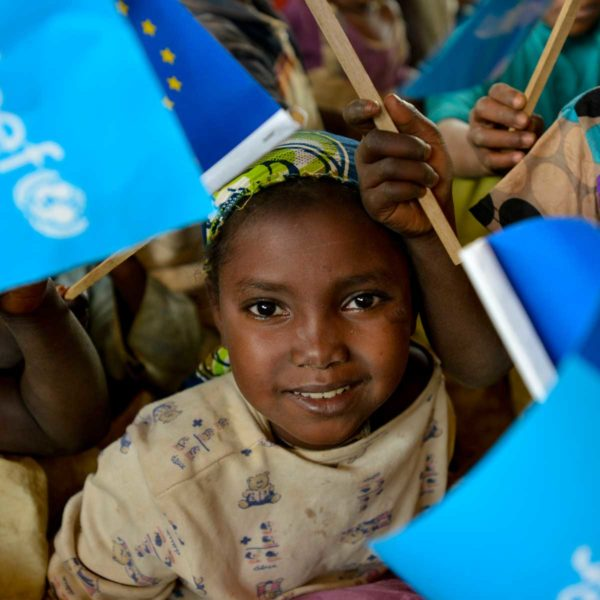 A smiling girl is among children holding and waving Unicef flags in a learning and protection space in Cameroon for refugees from the Central African Republic. Photo: Unicef 2015 Rich