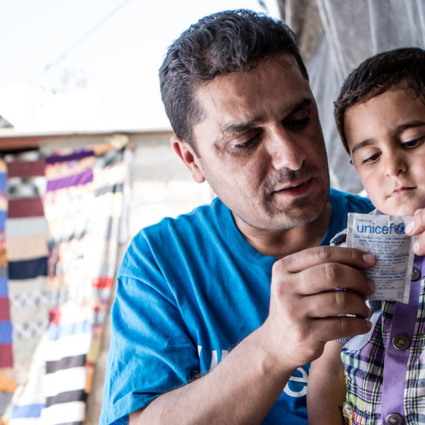 Iraq, May 2013. UNICEF worker Abduljabar prepares oral rehydration salts for four year old Ahmed. Ahmed lives with his brother and parents in a small room amongst five other families in the Domiz refugee camp in Northern Iraq. Domiz is situated near the city of Dohuk, about forty miles from the Syrian border. Approximately 40,000 Syrians are living here, in facilities provided for around half that number. Unicef 2013 Schermbrucker