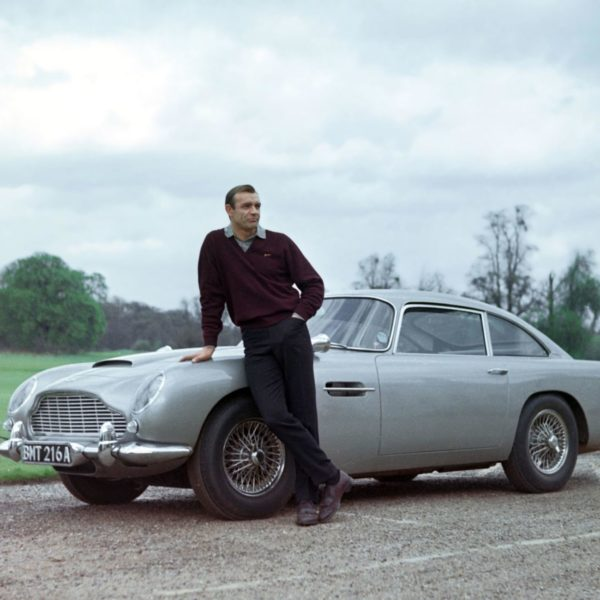 Sean Connery standing by an Aston Martin in Goldfinger
