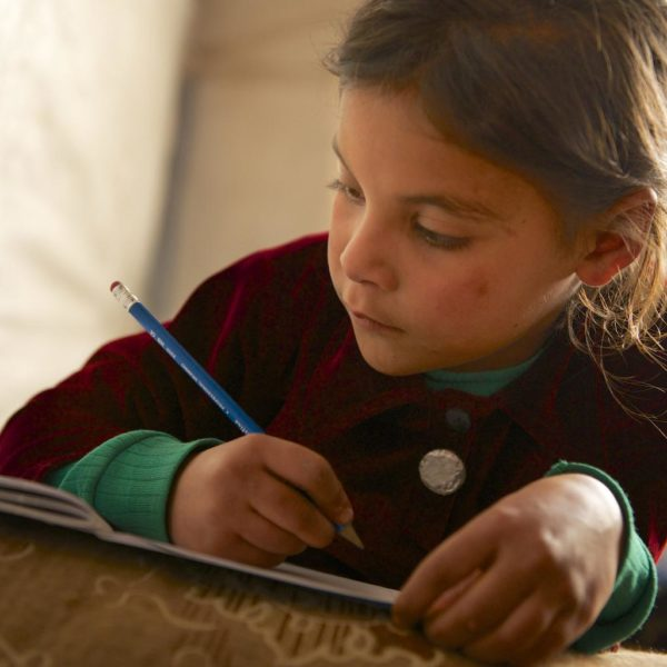 A young child completes homework in the tent she shares with 16 family members, in Dalhamieh, Syria. Photo: UNICEF/2013/Noorani