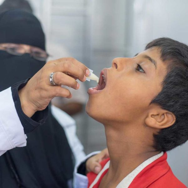 Emergency staff give a boy a cholera vaccine in Yemen
