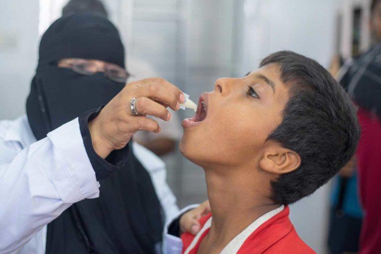 Emergency staff give a boy a cholera vaccine in Yemen